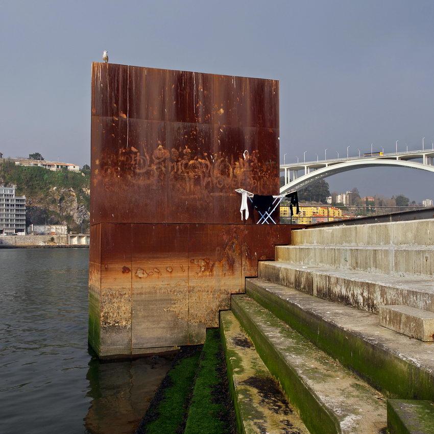 Escultura gigante em ferro com a forma de um paralelipípedo. Ao fundo a ponte da Arrábida