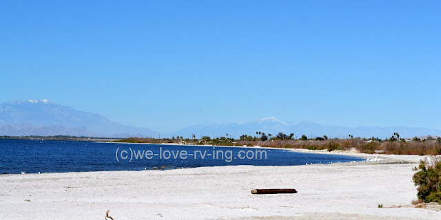 White sand along the beach and snowcapped mountains for background.