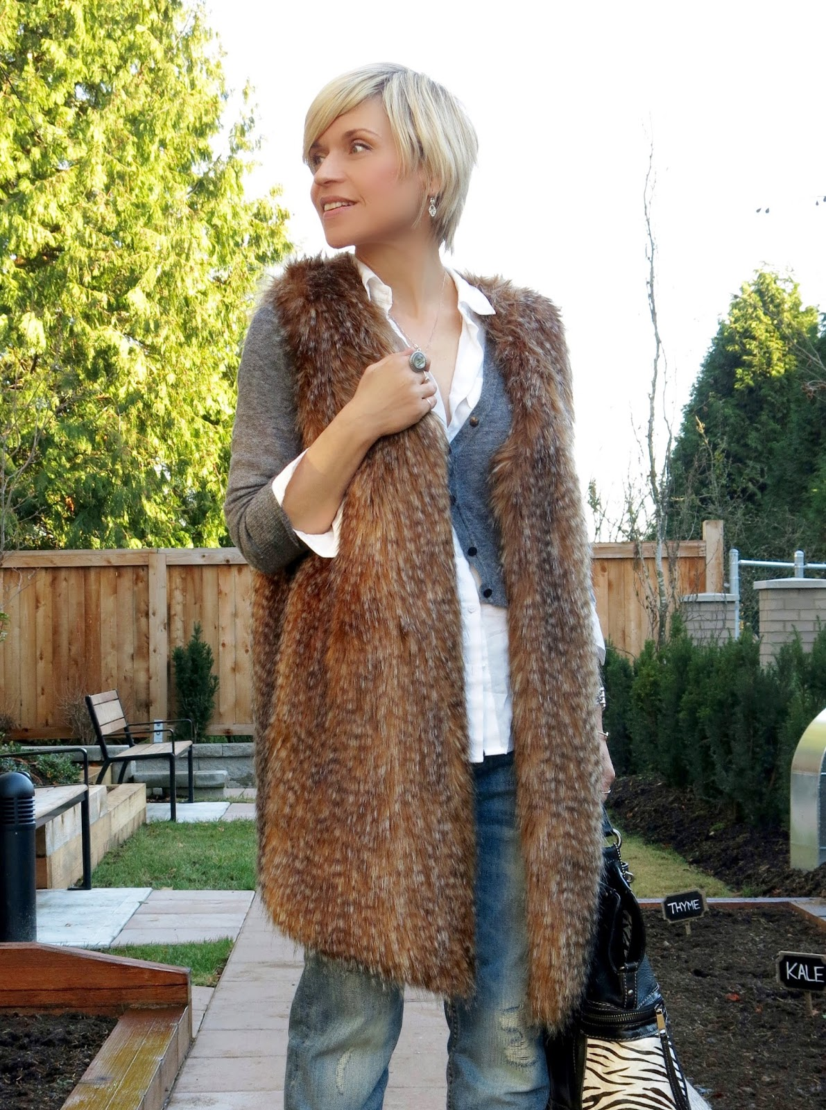 styling boyfriend jeans with a white shirt, shrunken cardigan, and furry vest