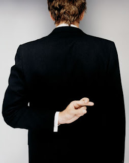 photo image of a person on a suit from behind. the person is making a hand gesture indicating that it is uttering a lie.