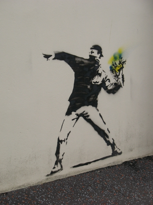 Banksy stencil painting of man with mask throwing bouquet of flowers