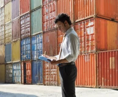 A business man taking notes of shipping containers.