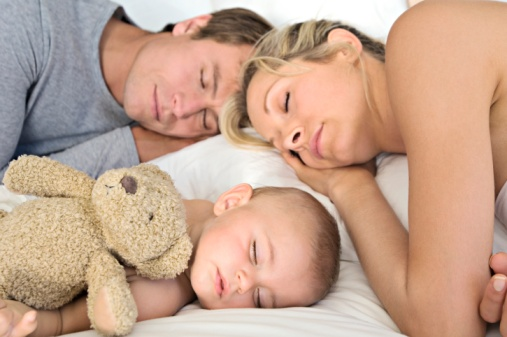 Husband, wife and baby sleeping peacefully.