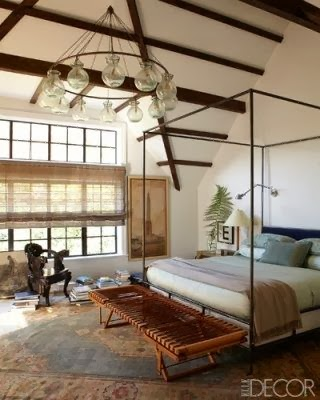 wrought iron four poster bed. high ceiling with rustic wood beams
