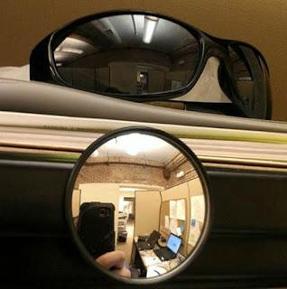 Espelho convexo ou óculos escuros para saber quem está vindo por trás no trabalho