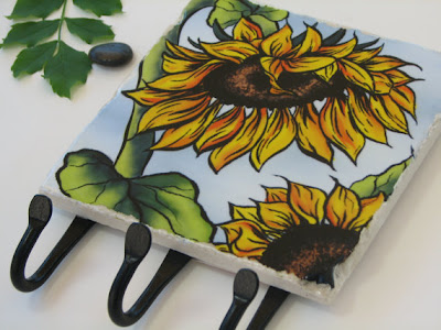 tile with sunflower painting, and three iron hooks