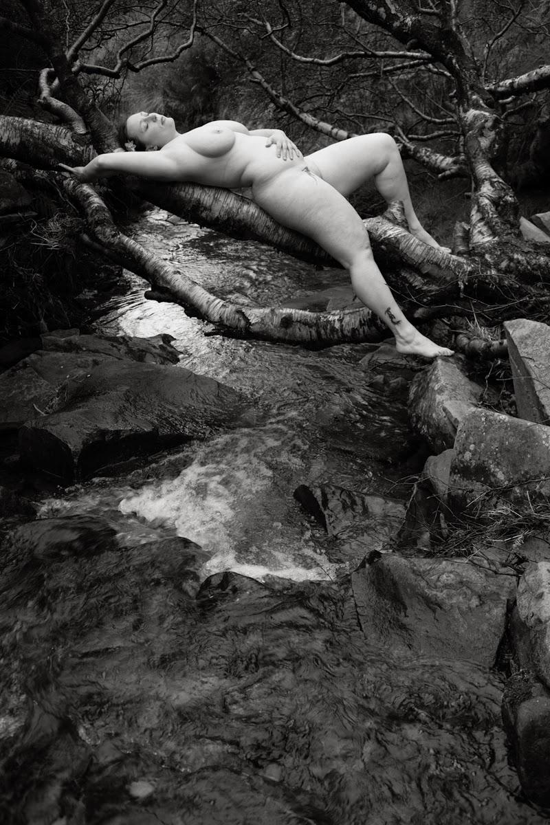 femme nue allongée sur une branche au dessus d'une rivière photo en noir et blanc