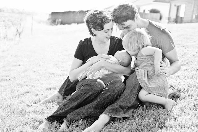family sitting in grass with toddler and newborn