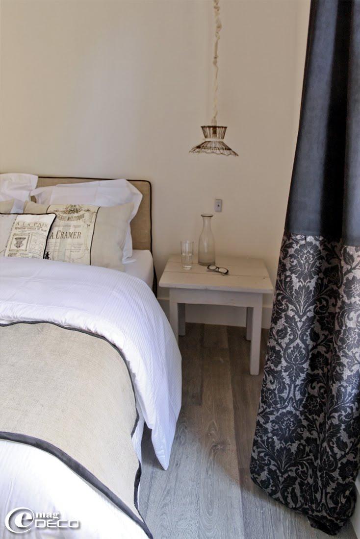 Dans une chambre décorée par Nathalie Vingot Mei, des rideaux noirs confectionnés Véronique Lavagne, une tête de lit houssée en lin gansée de noir réalisée par Brigitte Puaud Esseyric