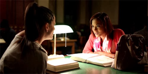 Zoey and Aubrey, played by Renae Leniece, sit in the light of a lamp at one of the large tables in the room.