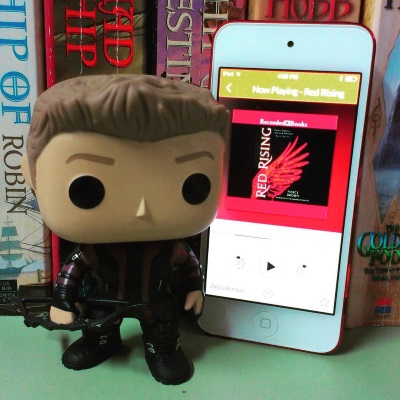 A four-inch tall bobblehead of Hawkeye stands next to a red-bordered iPod with Red Rising's cover on its screen. The bobblehead wears a purple and black jacket over black pants and strappy black boots. He carries a black bow. The book's cover features a red wing against a black background.