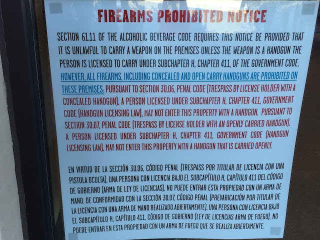 Panneau en anglais et espagnol, placé à l'entrée du magasin Whole Foods à Colleyville, Tx, interdisant l' entrée du magasin aux personnes portant une arme de poing, ou open carry.