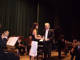 Sara e o maestro João Carlos Martins, no palco, em frente ao piano e à orquestra, no Teatro Nacional em Brasilia, 2007.