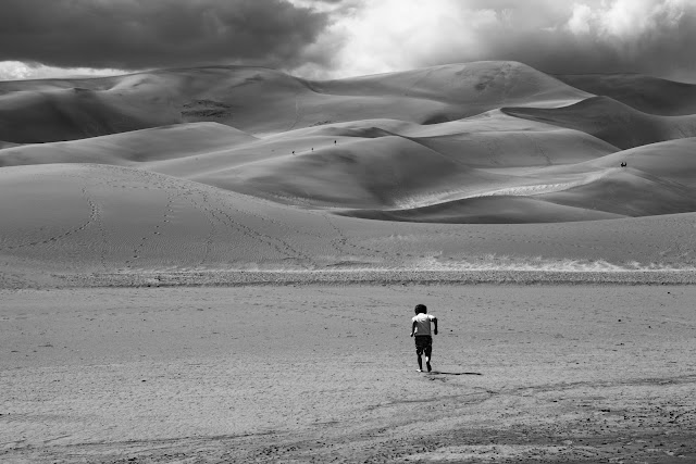 A boy running in the sand toward the huge dunes at Great Sand Dunes National Park.