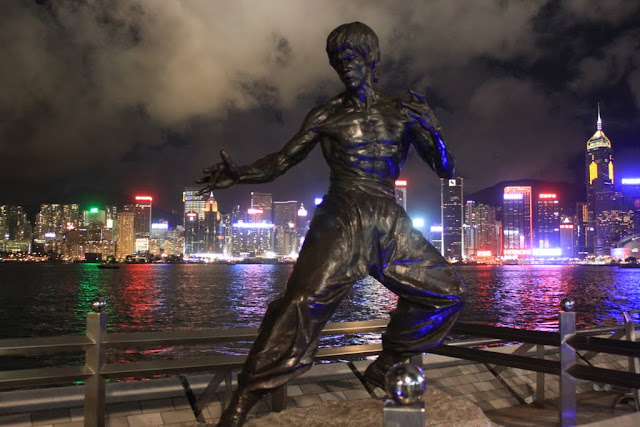 Bruce Lee statue at Avenue of Star with beautiful lighted skyscrapers at night in Hong Kong