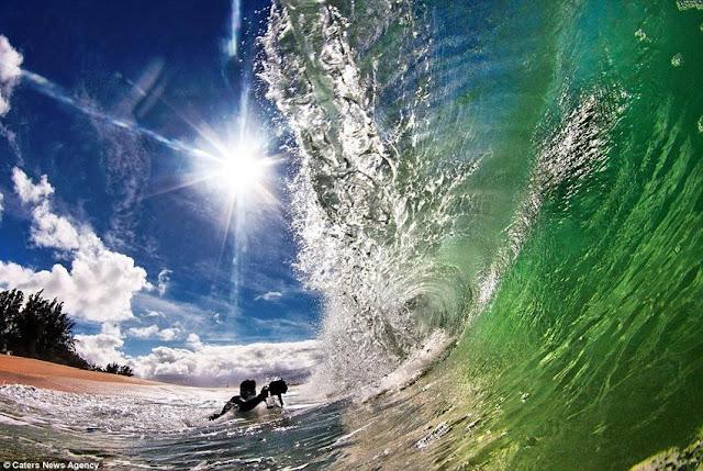 человек фотографирует волну