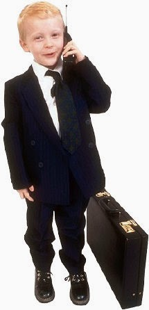 A kid in a suit, with a briefcase, on a cell phone