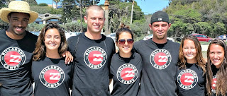 Group of camp counslors wearing their staff t-shirts and standing together on the beach with their arms around each other.
