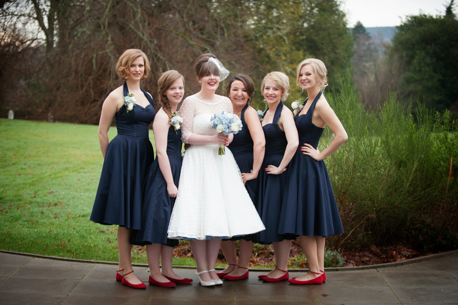 Bride and her bridesmaids at Achnagairn House in the Scottish Highlands. Bridesmaids wearing red shoes with fifties style dresses