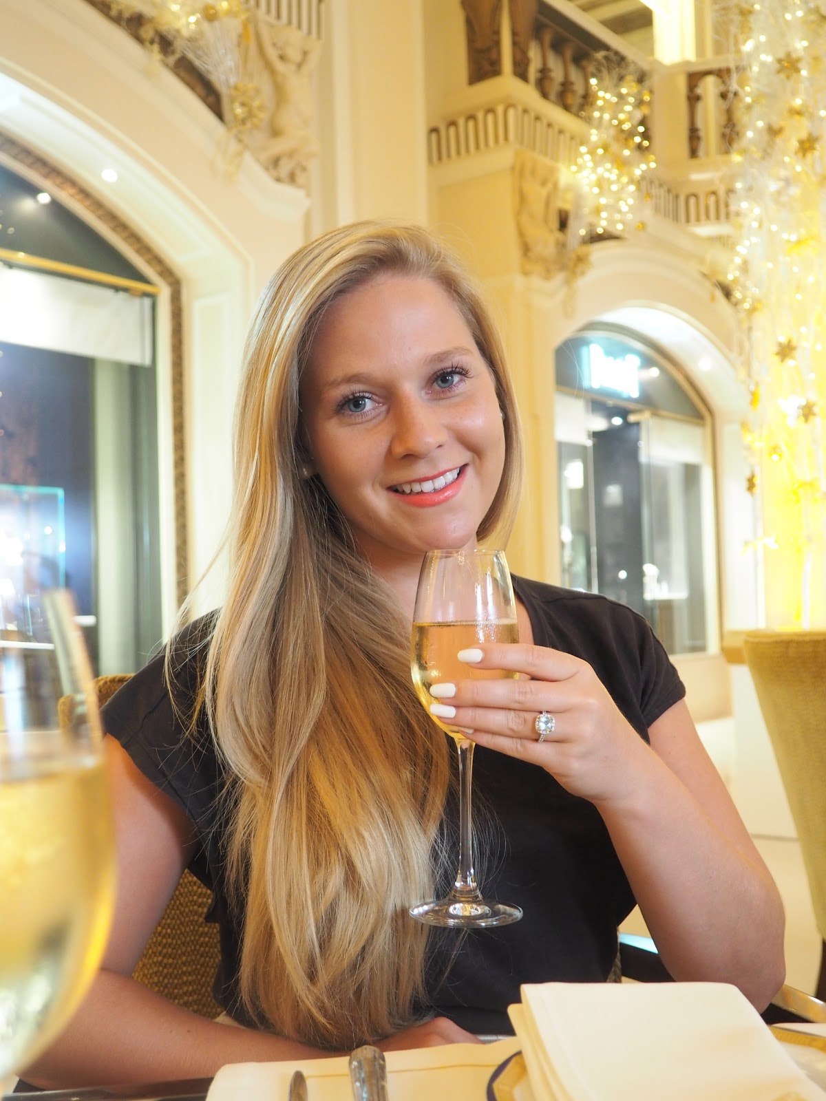 Girl sipping champagne in The Lobby, Peninsula Hotel, Hong Kong