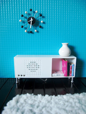 Modern dolls house miniature scene with a sideboard stereo unit.