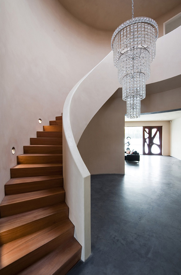 Photo of round wooden staircase by the white wall leading to the upper floor