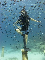 try dives in Cyprus; Diver feeds fish underwater