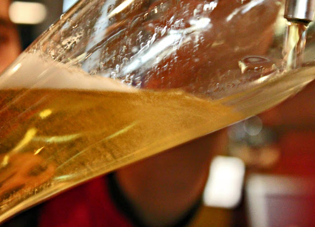 beer  being poured into a tall glass