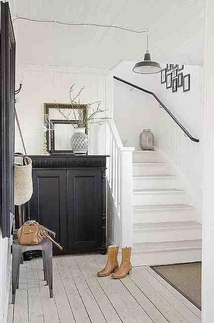 Skandynawskie wnętrze, drewniana podłoga z białych desek, metalowy taboret, białe schody, białe wnętzre i czarna komoda