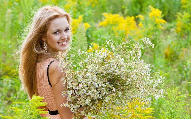 Achtergrond met mooie blonde vrouw met lang haar en bos bloemen in de lente