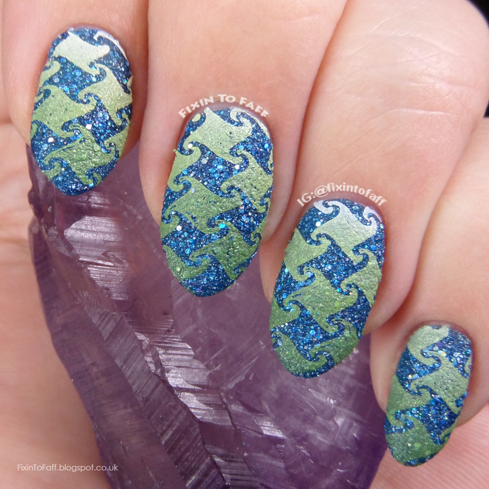 Gradient stamped houndstooth print over blue textured glitter base nail art.