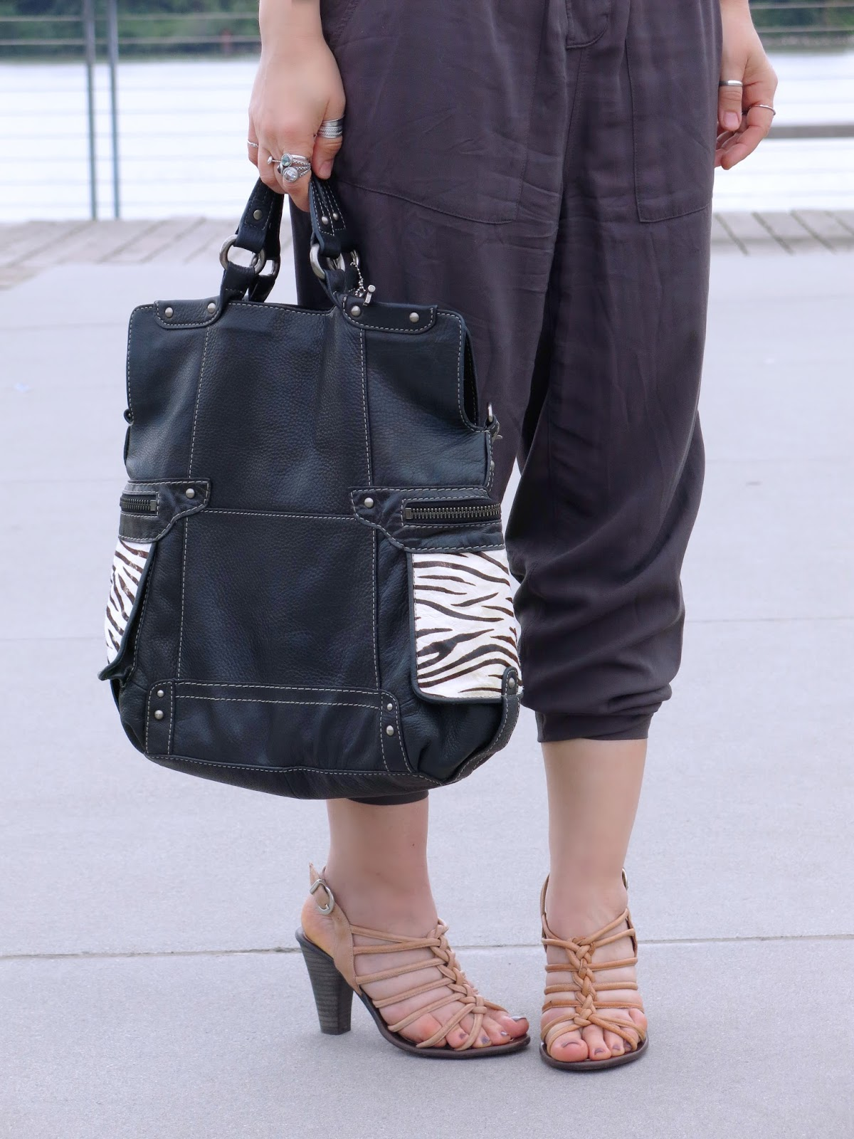 styling a utility-style jumpsuit with strappy nude sandals and a zebra-striped bag