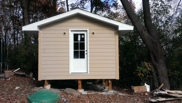 Outdoor sauna with finished siding and roofing.