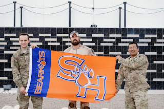 Bearkats serving in Afghanistan hold up the SHSU flag.