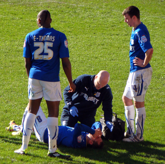 A footballer on the ground holding his head, attended to by a physio