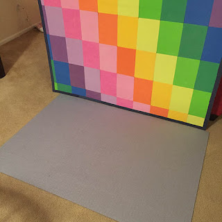 Large puzzle laying face down on a carpeted floor with a rainbow colored framed puzzle mat standing behind it