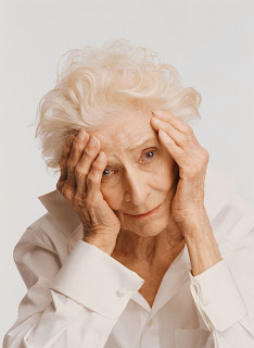 Confused elderly woman with her head in her hands.