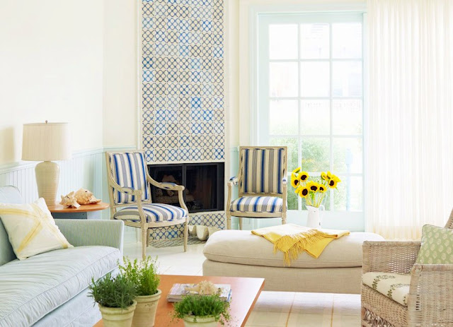Living room with fireplace covered in blue, white and yellow antique Portuguese tiles, with two upholstered , a striped sofa, a wicker armchair, wood coffee table, taupe ottoman and large window covered by white curtain