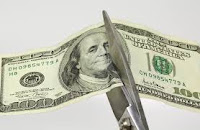 Photo of a 20 dollar bill being cut in half with scissors