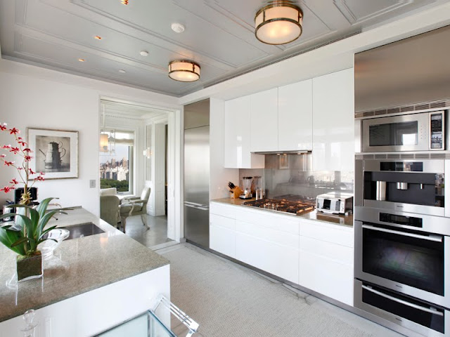 sleek kitchen outfitted with many modern conveniences: stainless appliances, glossy white cabinets and an island