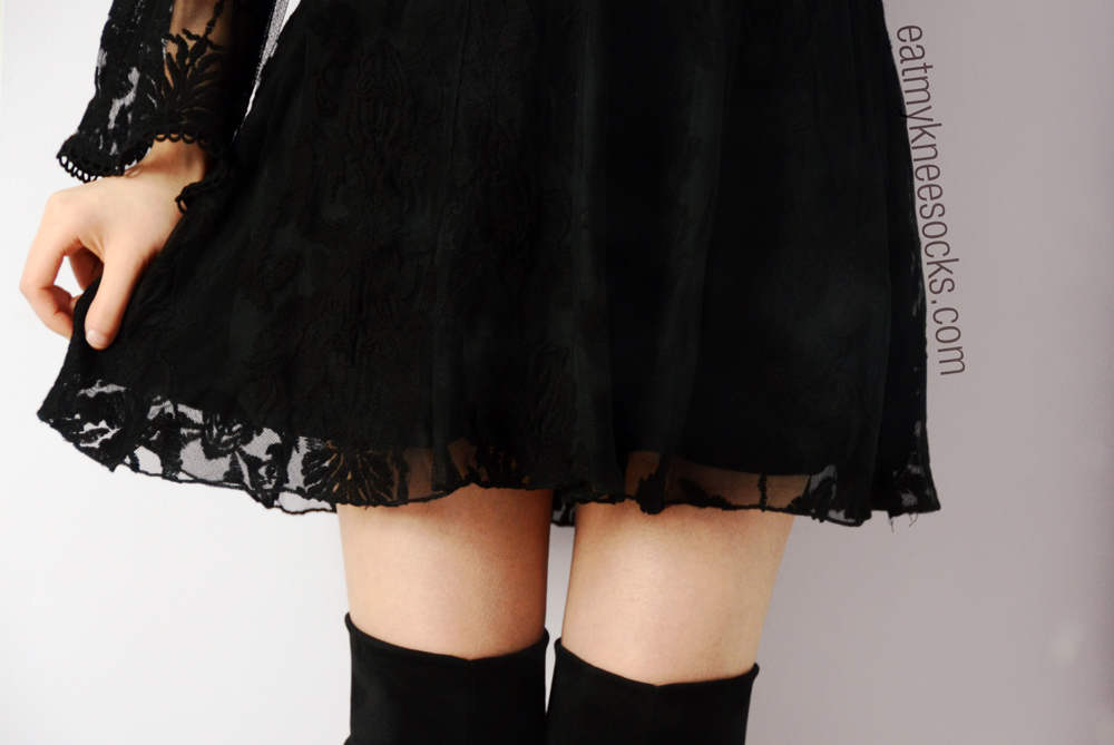 Close-up of the black embroidered floral lace hemline on this SheInside bell-sleeved dress.