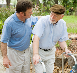 A man helps his father use a walker in a park