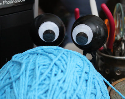 googly eyes hiding behind yarn
