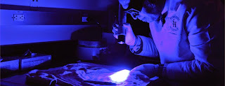 Faculty examine biological materials on clothes under a blue light.