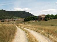 En primer terme Cal Mestre, a la seva esquerra les granges del Català i al fons, enlairades, les antenes d'El Remei