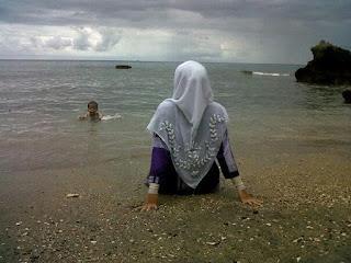 perempuan memandang pantai