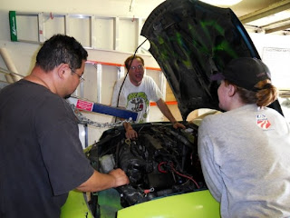 team members attaching hoist to pull out race car engine