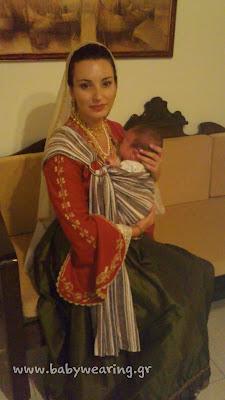 Με το νεογέννητο μωράκι της στο μάρσιπο sling και την παραδοσιακή φορεσιά, μια πανέμορφη μαμά!