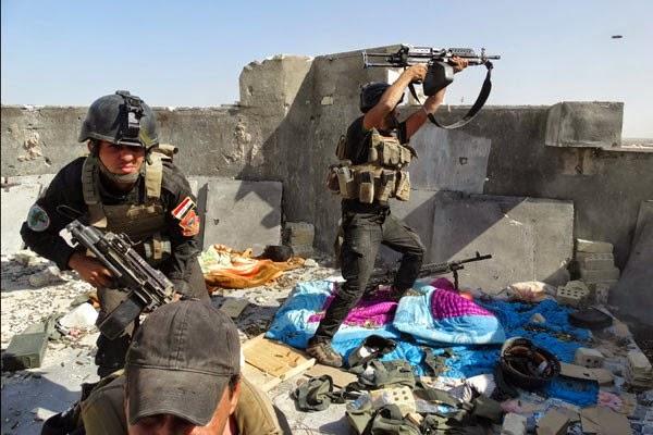 Anggota Pasukan Operasi Khusus Irak mengambil posisi saat bentrok dengan kelompok Negara Islam Irak dan Mediterania (ISIL) yang terkait dengan Al-Qaeda di Ramadi, Irak, Kamis (19/6). (REUTERS/Stringer)
