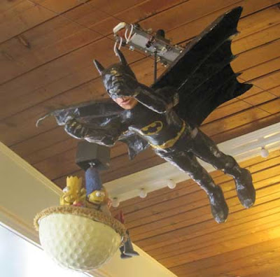 Papiere mache figure of Batman flying on wires near the ceiling